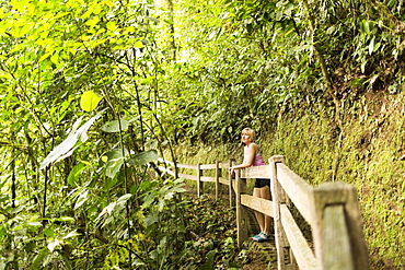Woman in forest leaning against wooden fence, Costa Rica