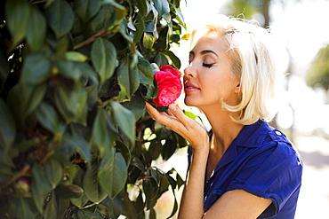 Woman smelling rose, Costa Mesa, California