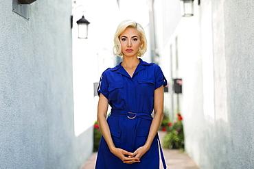Woman in blue dress posing on street between white buildings, Costa Mesa, California