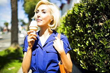 Woman walking with ice-cream, Costa Mesa, California