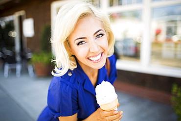 Portrait of smiling woman with ice-cream, Costa Mesa, California