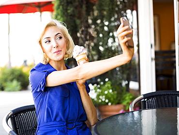 Woman photographing herself with ice-cream, Costa Mesa, California