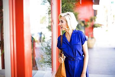 Woman in blue dress looking at window display, Costa Mesa, California
