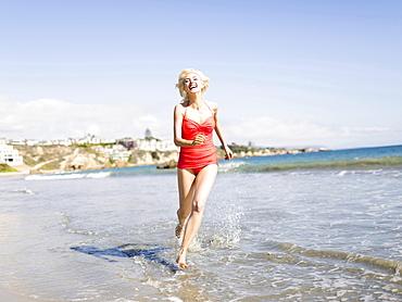 Blond woman running on beach, Costa Mesa, California