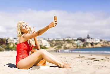 Blond woman taking selfie on beach, Costa Mesa, California
