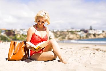 Portrait of blond woman reading book on beach, Costa Mesa, California
