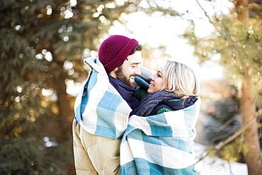 Couple wrapped in blanket hugging outdoors, Salt Lake City, Utah