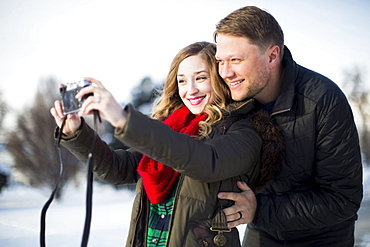 Woman photographing herself and man
