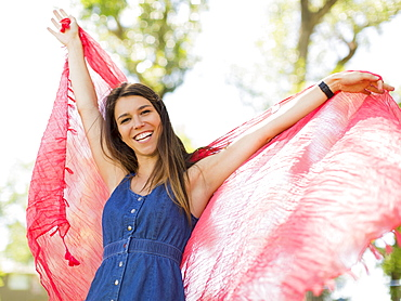 Young woman playing with scarf in park, Salt Lake City, Utah, USA