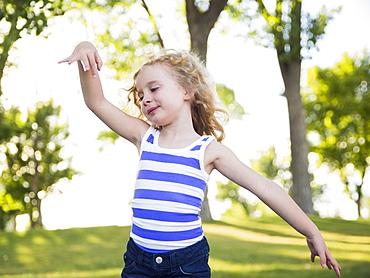 Blonde girl (4-5) dancing in park, USA, Utah, Salt Lake City