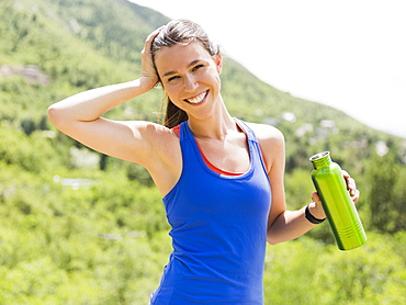 Portrait of female jogger holding bottle, USA, Utah, Salt Lake City