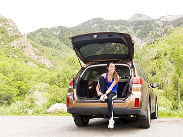 Woman wearing sportswear sitting at car trunk with dog, USA, Utah, Salt Lake City