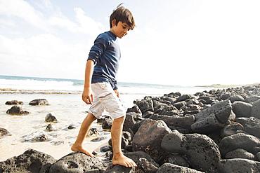 Boy (10-11) walking on stones on beach, Kauai, Hawaii
