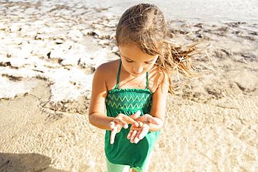 Girl (6-7) playing on beach, Kauai, Hawaii