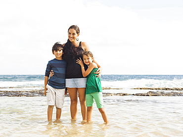 Portrait of girl (6-7) and boy (10-11) standing on beach with mother, Kauai, Hawaii