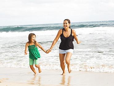 Girl (6-7) running on beach with mother, Kauai, Hawaii