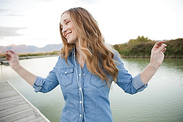 Portrait of young woman listening to mp3 player on jetty, Salt Lake City, Utah