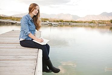 Portrait of young woman sitting on jetty, Salt Lake City, Utah