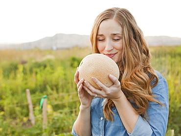 Portrait of young woman holding cantaloupe, Salt Lake City, Utah