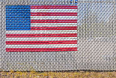 The American flag woven into a chain link fence, Charleston, OR