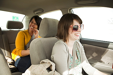 Two young women travelling by car