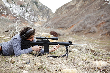 Man lying on front with weapon