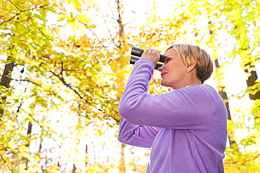 USA, New Jersey, Woman looking through binoculars in Autumn forest