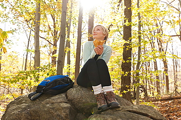 Female hiker resting on rock in forest