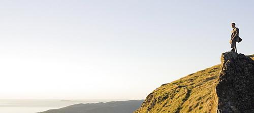 Businessman standing on rock overlooking ocean