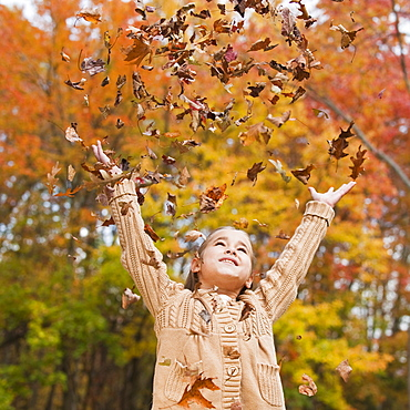 Girl throwing leaves