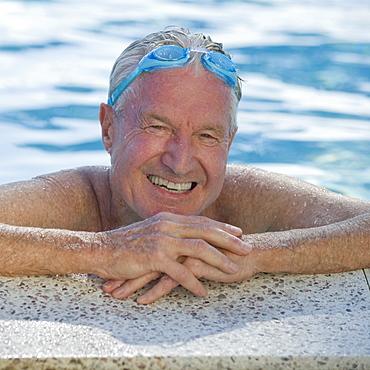 Senior man resting on edge of swimming pool