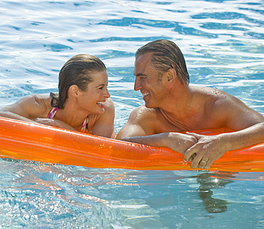 Couple resting on raft in swimming pool