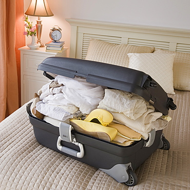 Full suitcase on bed