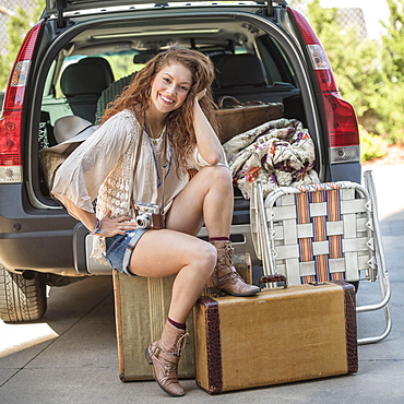 Portrait of young woman sitting on luggage near car