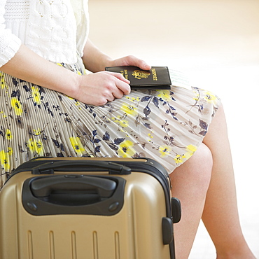 Close up of woman with luggage and passports