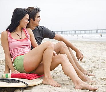 Couple sitting on surfboard at beach