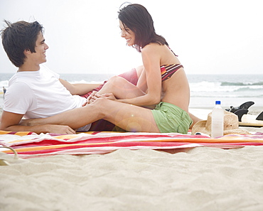 Couple sitting on blanket at beach