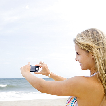 Woman taking photograph of ocean