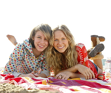 Two young women laying on beach