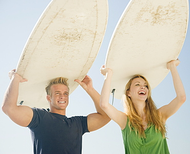 Couple holding surfboards on head