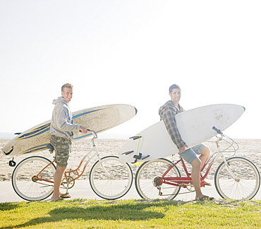 Two men with surfboards on bicycles