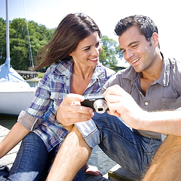 Couple sitting on dock looking at photos on digital camera