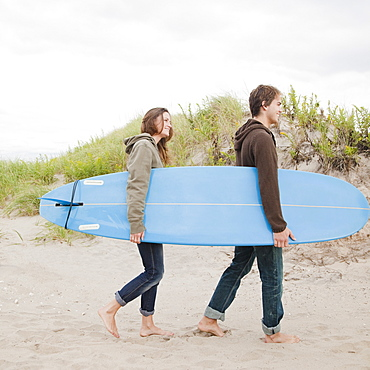 Couple carrying surfboard