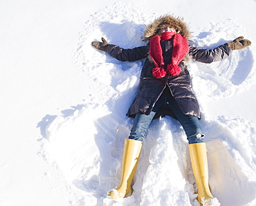 USA, New Jersey, Jersey City, young woman doing snow angel