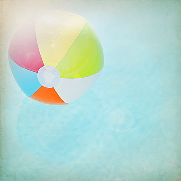 Close up of striped beach ball against water surface