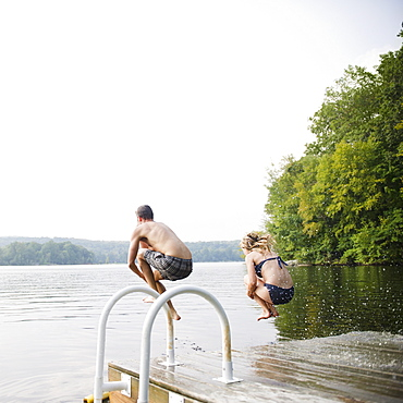 USA, New York, Putnam Valley, Roaring Brook Lake, Couple jumping from pier to lake
