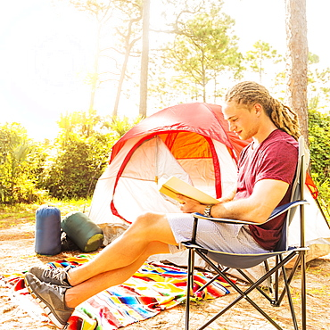 Man reading book in front of tent, Tequesta, Florida