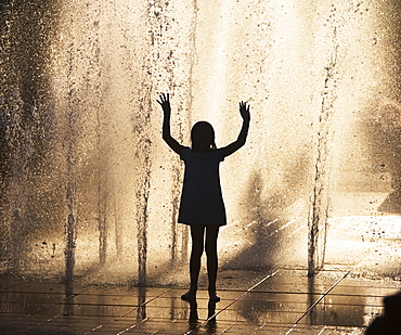 Silhouette of girl playing in fountain