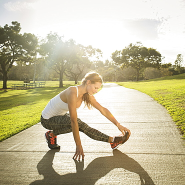 Woman stretching in park, Irvine, California