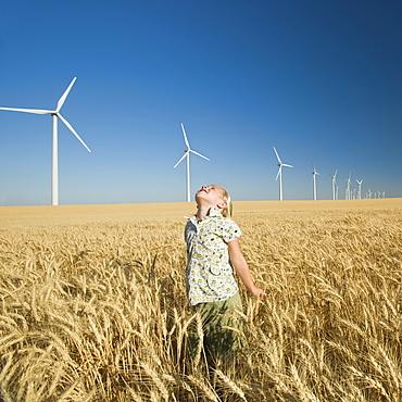 Girl looking to sky on wind farm